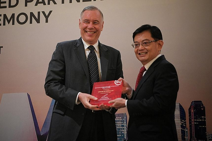 Applied Materials chief executive and president Gary Dickerson receiving the Distinguished Partner in Progress Award on behalf of the US firm from Deputy Prime Minister Heng Swee Keat yesterday. ST PHOTO: MARK CHEONG