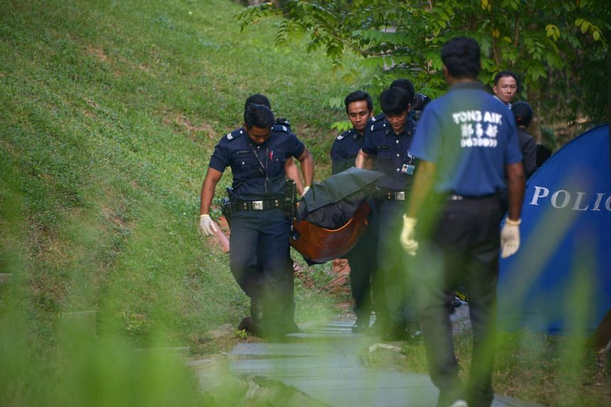 In a file photo taken on Aug 27, 2015, near Kheam Hock Road in Bukit Timah, the body of Indian national Chinniah Ganeshan is seen being taken away by police officers.
