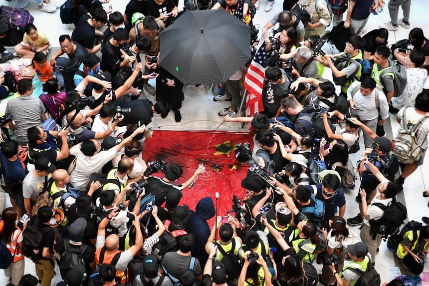 Protesters deface a Chinese flag in New Town Plaza, Shatin in Hong Kong on Sept 22, 2019.