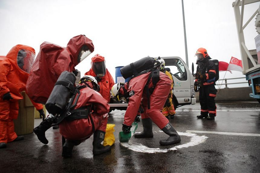 """Rescue teams wearing hazmat suits descend on the scene of an """"accident"""" involving a lorry carrying drums of hydrochloric acid and a tanker filled with ammonia gas."""