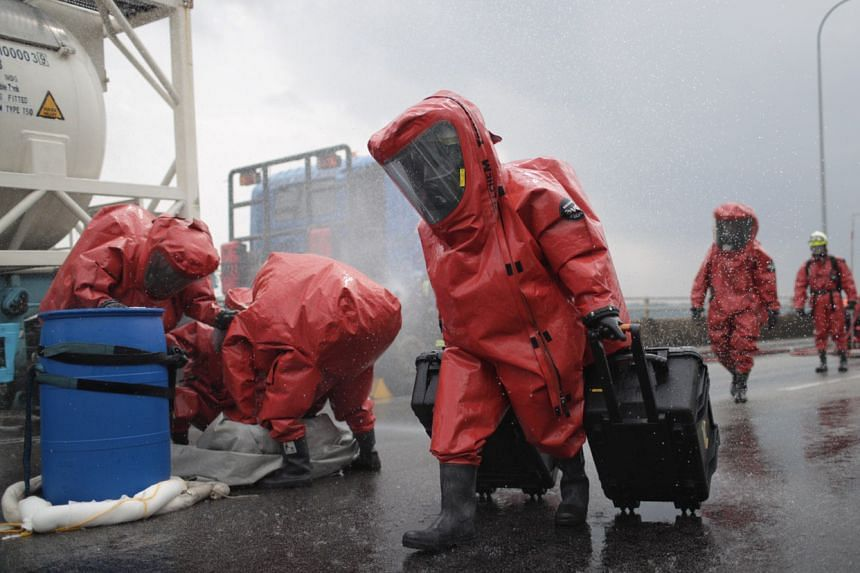 """One group of SCDF personnel in hazmat suits isolate a ruptured drum containing hydrochloric acid while another carries more equipment to other team members trying to contain the location where a """"chemical spill"""" occurred on Sept 25, 2019."""