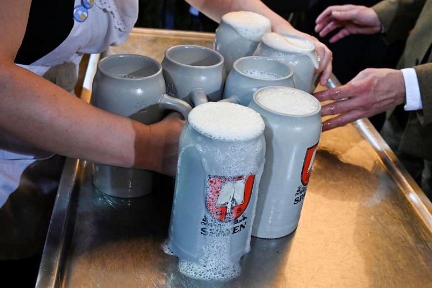 In a photo taken on Sept 21, a waitress takes beer mugs at the opening of the Oktoberfest festival.