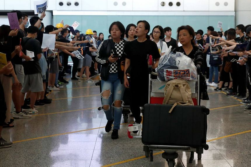 In this photo taken on July 26, 2019, demonstrators offer leaflets to arriving tourists during a protest at Hong Kong airport. Paranoid they could be targeted and wary after seeing footage of the protests, many Chinese tourists are staying away from
