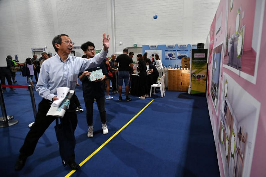 Mr Lim Hin Teck, 63, financial advisor, playing the Beat the Bug with game at the Panasonic booth, after collecting his race pack.
