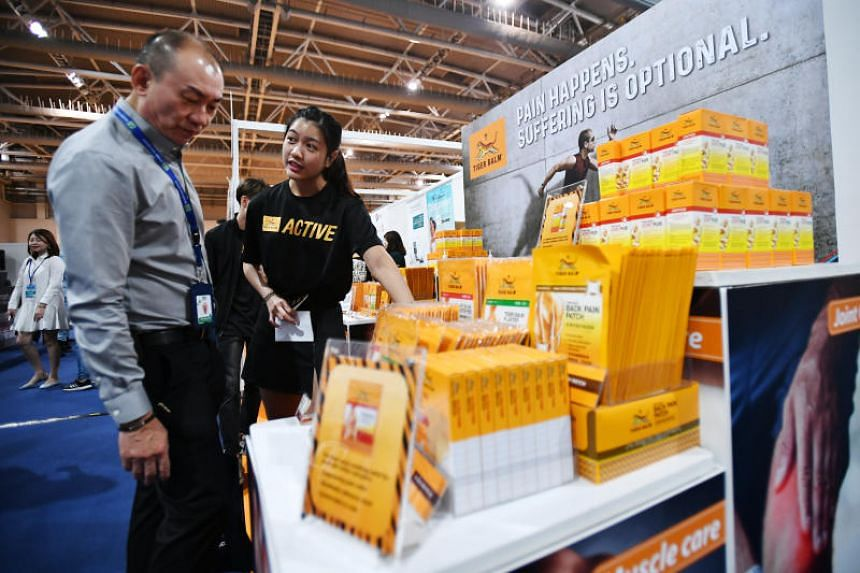 A participant browsing through products at the Tiger Balm booth.