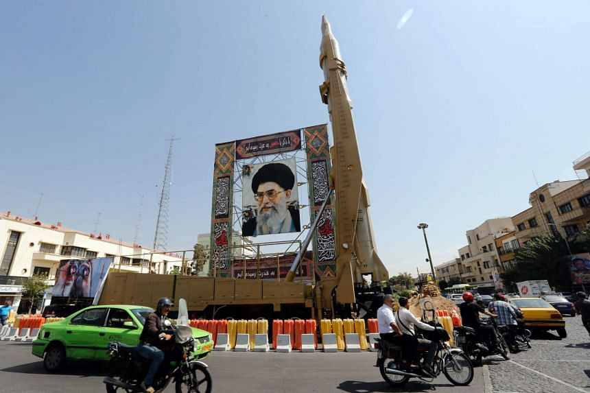 "A Shahab-3 surface-to-surface missile is pictured on display next to a portrait of Iranian Supreme Leader Ayatollah Ali Khamenei at a street exhibition by Iran's army and paramilitary Revolutionary Guard celebrating ""Defence Week""."