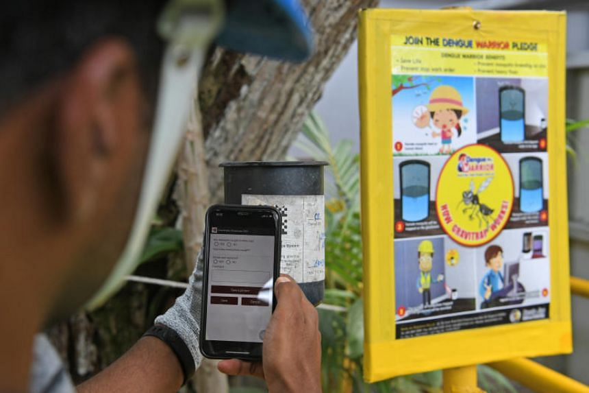 A worker scans his mobile phone on the GraviTreks Mosquito Surveilance system to get the latest updates inside the Tanjong Katong MRT Station worksite.