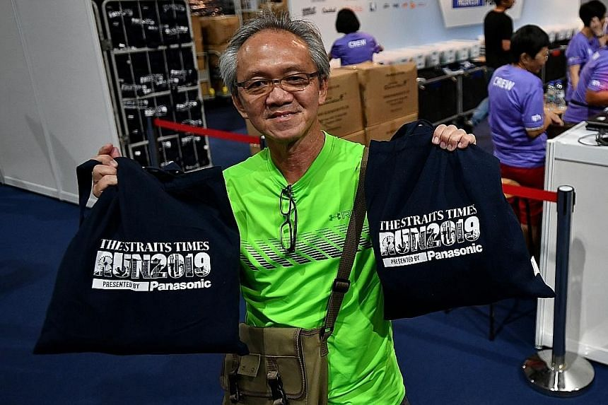 ST Run participants collecting their race packs at the OCBC Arena yesterday. They were kept engaged and entertained during the collection, with the run's presenting sponsor Panasonic rolling out a game at its booth, and the first 200 participants win