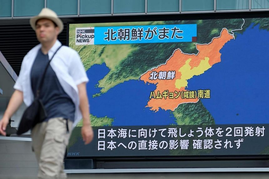 In a photo taken on Aug 10, 2019, a pedestrian walks past a giant screen in Tokyo reporting about North Korea's missile launch earlier in the day.