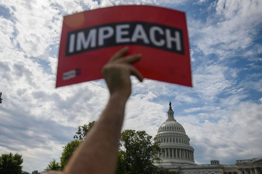 A protester holds up a sign outside the US Capitol building on Capitol Hill in Washington, DC, on Sept 26, 2019.