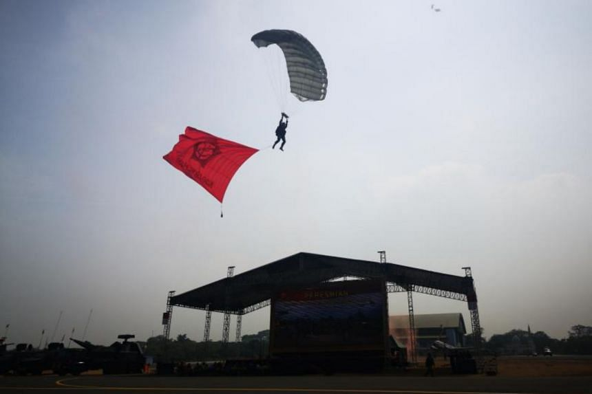 Indonesian armed force holding a parachute demonstration and fighter jet fly-by low pass during the Sept 27 inauguration of three three-star officers who will lead the country's newly formed Kogabwilhan, joint defence groups.
