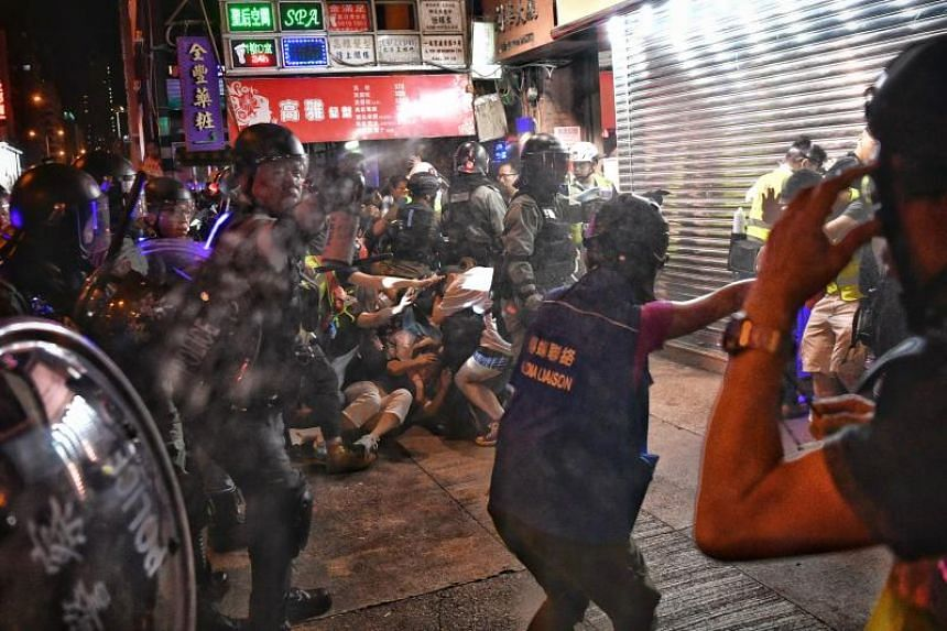 In a photo taken on Sept 22, a police officer uses pepper spray on the media during the arrest of a bystander who had berated the police in Nathan Road in Hong Kong.
