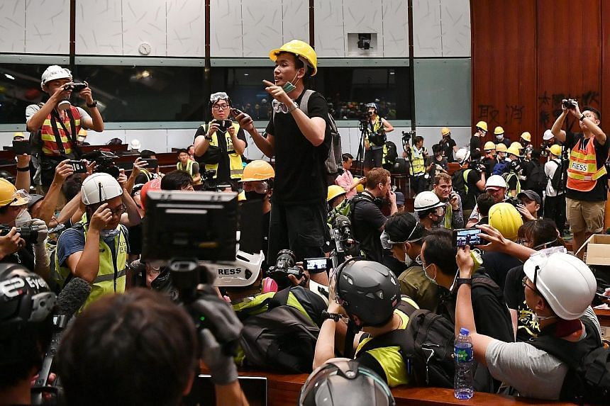 Mr Brian Leung Kai-ping, 25, openly revealed his identity, despite fellow protesters warning him against removing his mask, as he felt it was the defining moment of the night. PHOTO: LIM YAOHUI/THE STRAITS TIMES, SINGAPORE