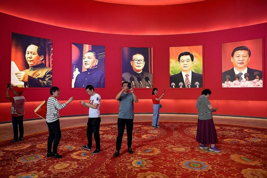 Visitors at a Beijing exhibition marking the country's achievements on Thursday, ahead of the 70th anniversary of the founding of the People's Republic of China on Oct 1. On display were portraits of (from left) past Chinese leaders Mao Zedong, Deng