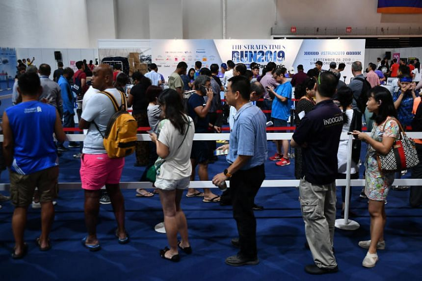 Participants of The Straits Times Run 2019 queueing to collect their race packs at the OCBC Arena on Sept 26, 2019.