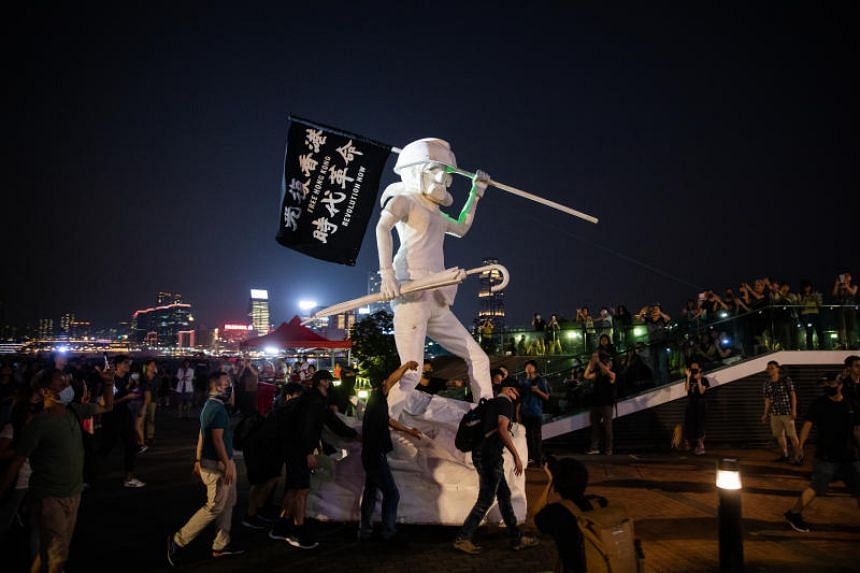 Protesters move a sculpture at Tamar Park in Hong Kong on Sept 28, 2019.
