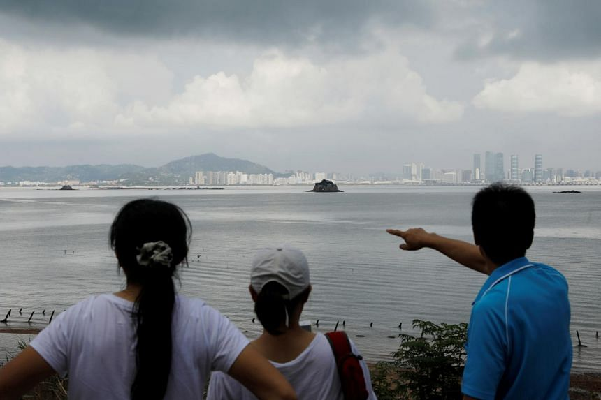 A tourist points at China's Xiamen from a former military fort on Lieyu island in Taiwan.