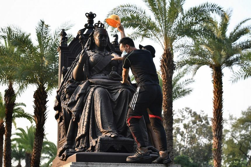 Protesters putting a yellow construction helmet on the head of the statue of Queen Victoria at Victoria Park on Sept 28, 2019.