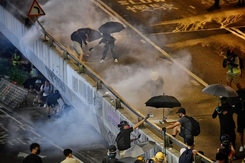 Protesters dousing tear gas canisters fired by police near the Legislative Council building in Hong Kong on Sept 28, 2019.