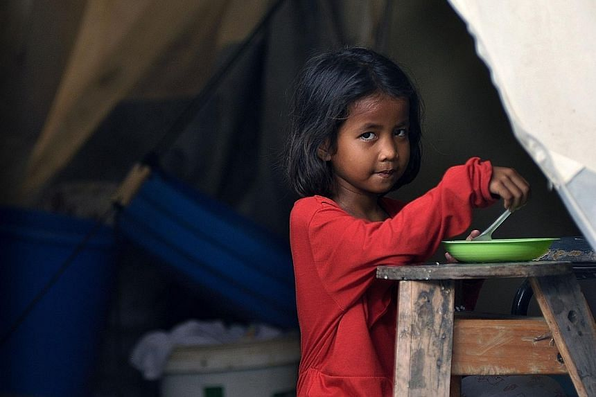 A girl having a meal in a makeshift shelter. Nearly 60,000 people lost their homes in the disaster.