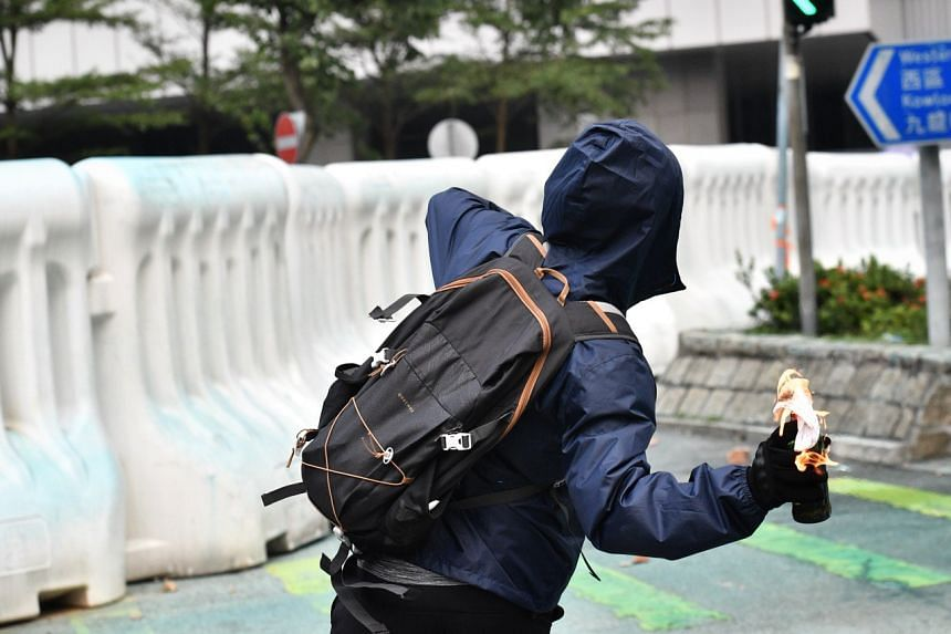 A protester throws a petrol bomb at the police behind the barrier at central government complex.