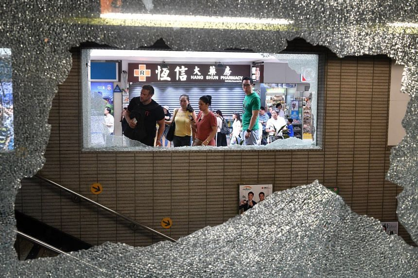 Tourists look at the damage caused by the protesters at Wan Chai Station.