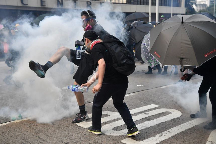 Protesters kick and douse a tear gas canister on Sept 29, 2019.
