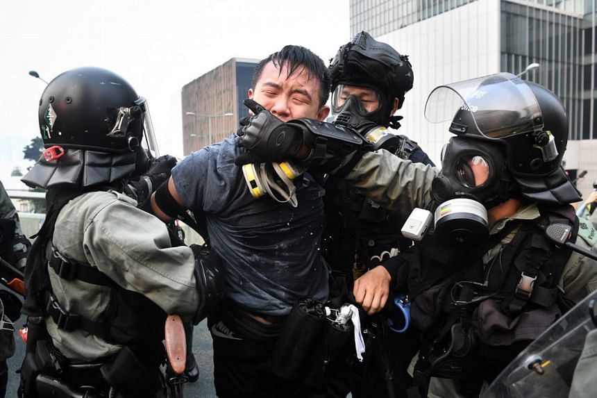 Police cover the mouth of a protester they arrested to stop him from speaking to the media at Harcourt Road on Sept 29, 2019.