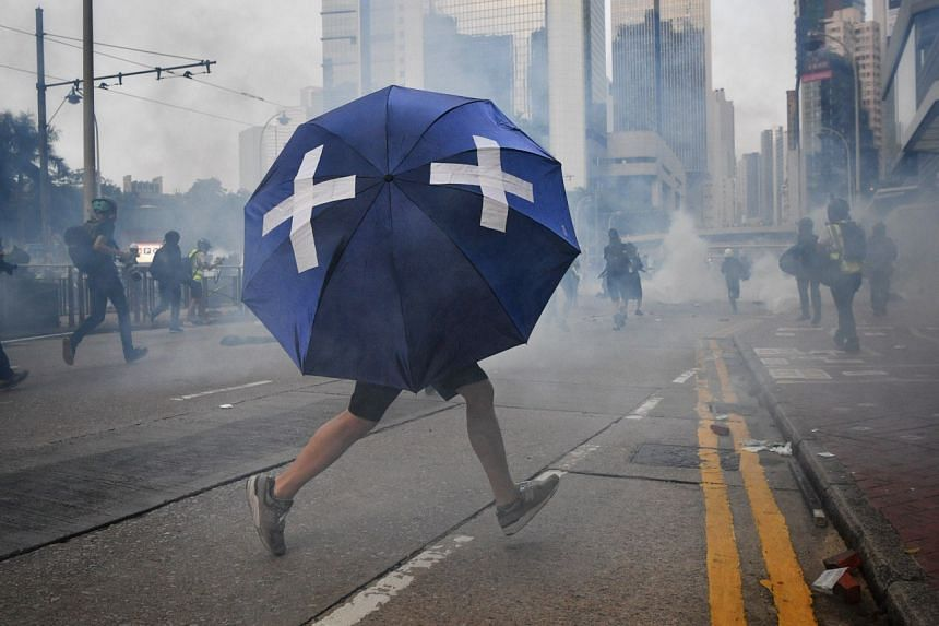 A medic uses a umbrella to shield himself as he runs through the line of fire on Sept 29, 2019.