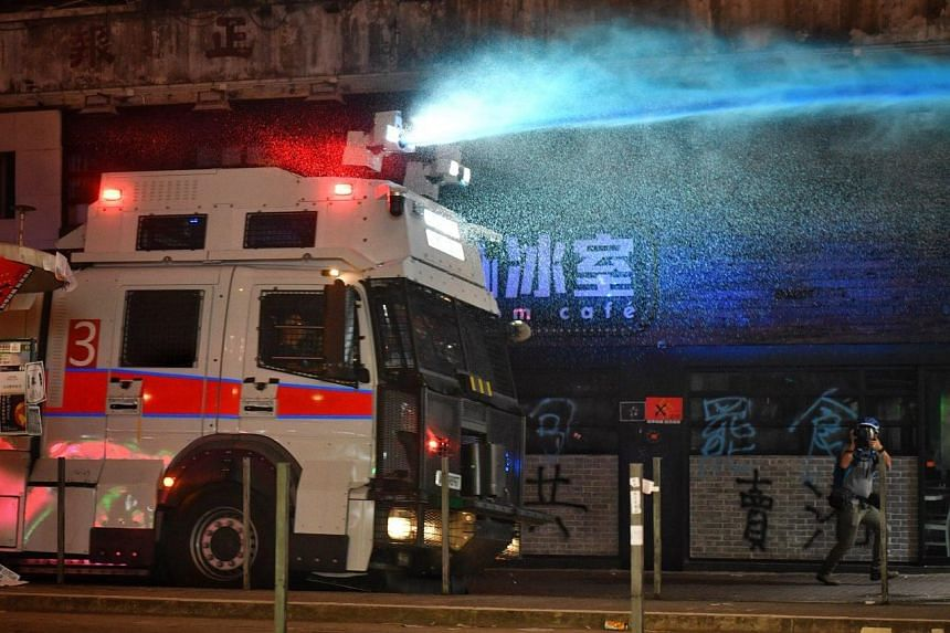 A water cannon, deployed by the Hong Kong police, shoots blue dye at protesters on Sept 29, 2019.