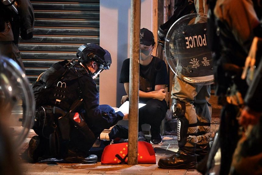 A protester has her belongings searched by the police along Causeway Bay on Sept 29, 2019.