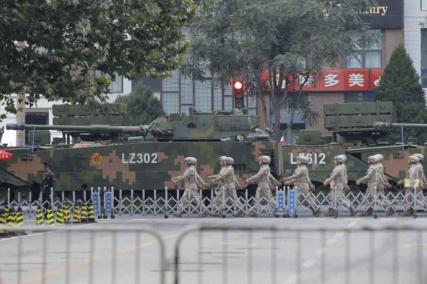 Soldiers walk past armoured vehicles parked along a street ahead a parade rehearsal event in Beijing, China, on Sept 21, 2019.