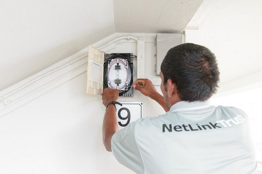 A NetLink Trust contractor doing installation work at a fibre optic cable connection point.