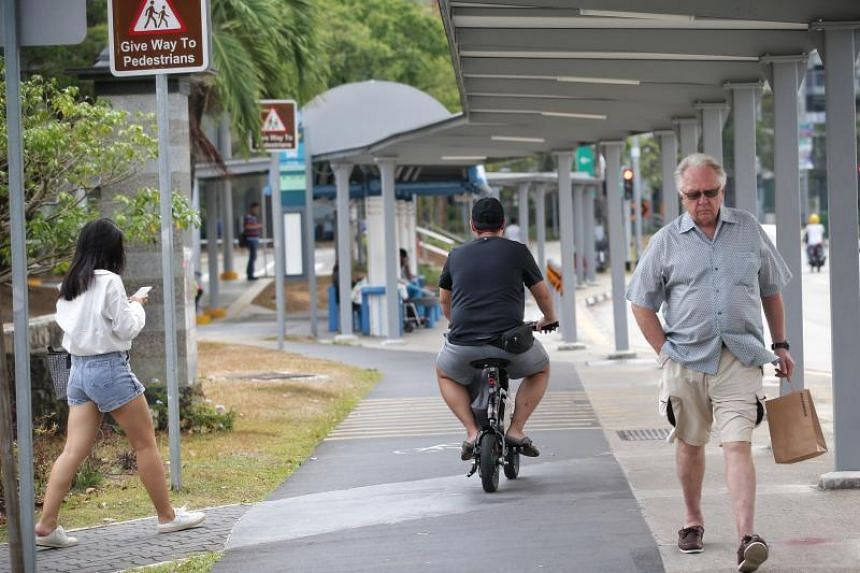 A PMD rider rides past pedestrians on shared path along Pasir Ris Central on Sept 27, 2019.