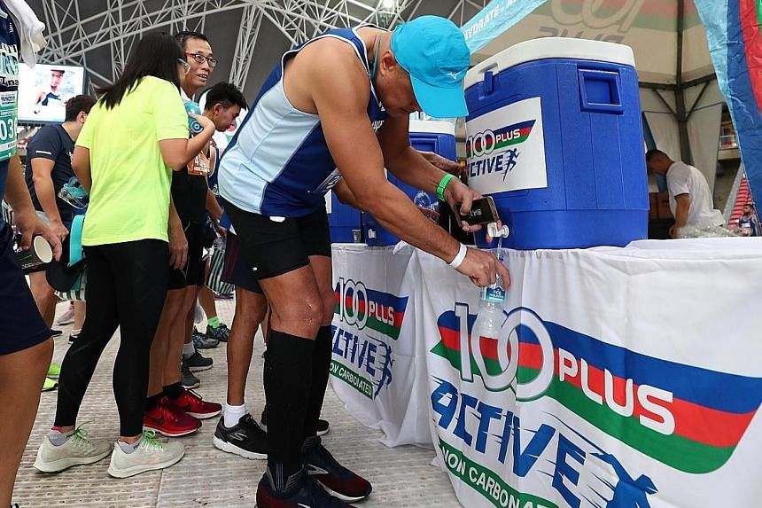 Runners quenching their thirst at the 100Plus station.