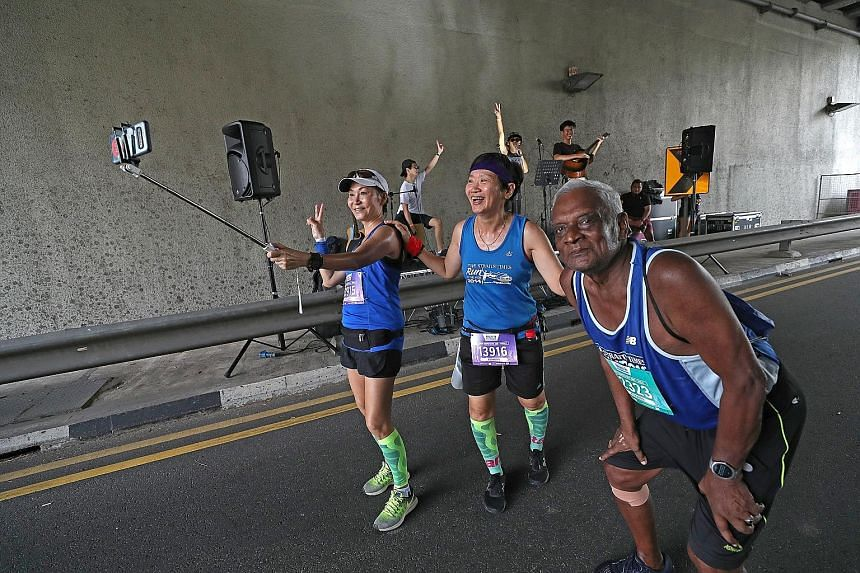 From left: Jessie Chong, 58, Merry Hui, 60 and G. Ramanatham, 80, having fun at the entertainment point near Crawford Street during their 10km event as folk and pop band The SlaCks perform.