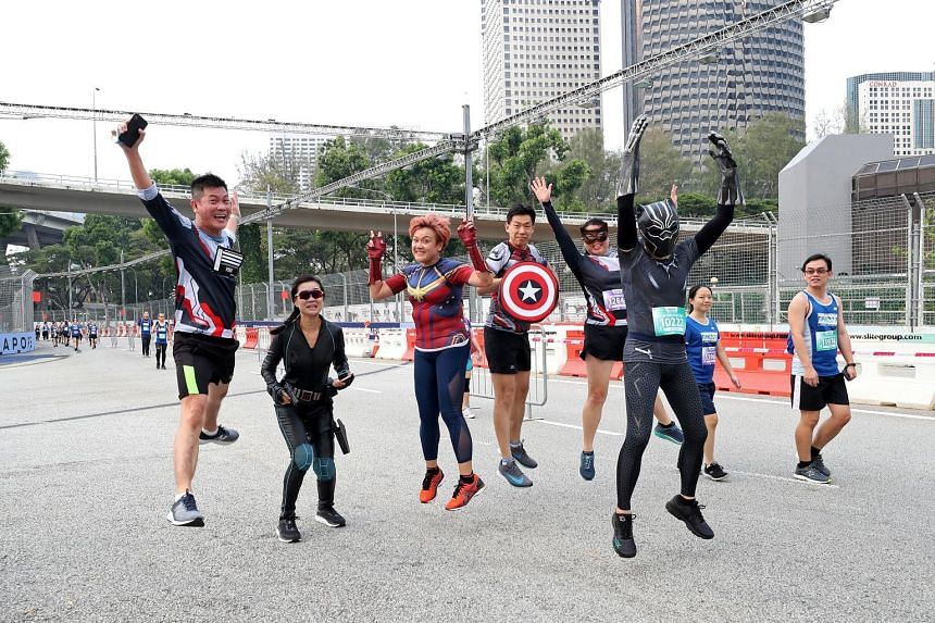 """Birthday girl J. Lee, in a Captain Marvel jersey, celebrating her 42nd birthday yesterday by running the 10km race with her """"superhero"""" friends. Here, they were seen along Republic Boulevard during the run."""