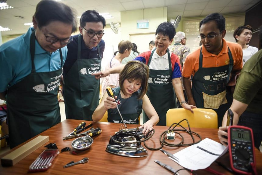 Senior Minister of State for the Environment and Water Resources Dr Amy Khor working on an iron with a screwdriver.