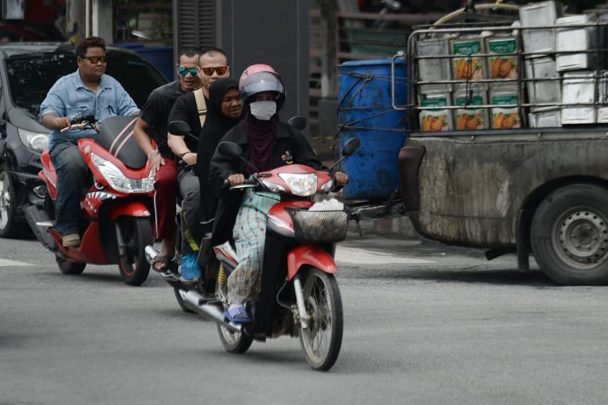 A motorist wearing a face mask during a commute through Thailand's southern province of Narathiwat on Sept 20, 2019. Pollution spikes caused by industrial emissions, construction, crop burning and vehicle fumes have rattled Thailand in recent years.