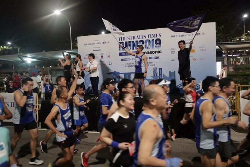 The Straits Times editor Warren Fernandez (on stage, second from right) flagging off the 18.45km race, on Sept 29, 2019.