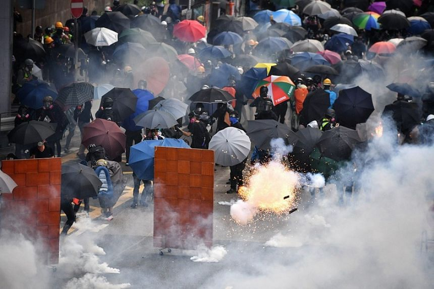 Anti-government protesters retreat as a tear gas canister explodes near Lippo Centre, Hong Kong, on Sept 29, 2019.