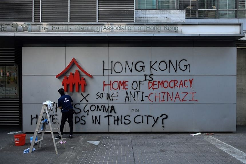 A worker cleans graffiti put up by protesters in Hong Kong on Sept 30, 2019, a day after the protest-wracked financial hub witnessed its fiercest political violence in weeks.