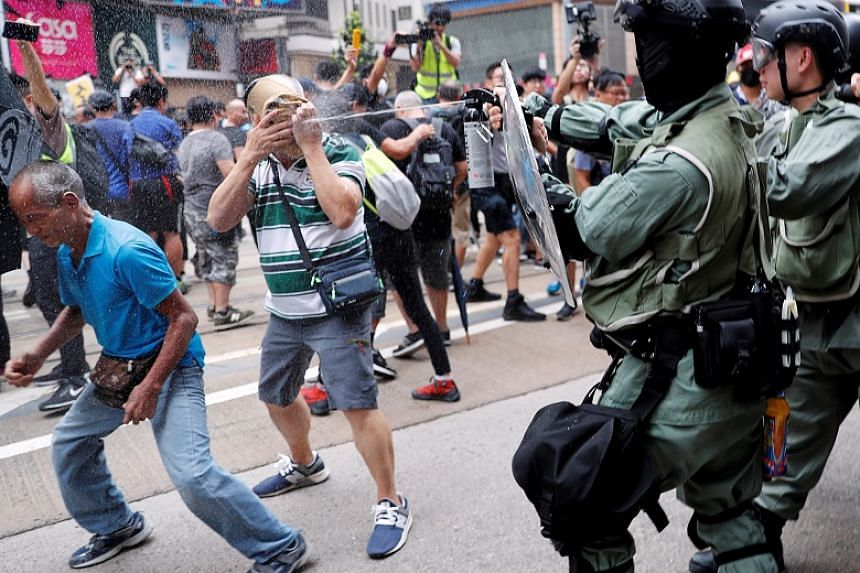 A riot police officer pepper sprays an anti-government protester during a demonstration at Causeway Bay in Hong Kong on Sept 29, 2019.
