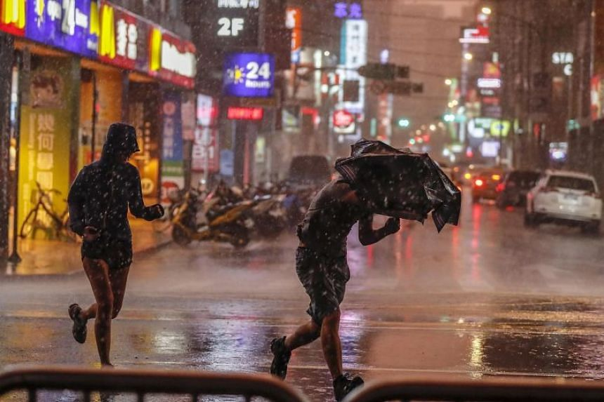 In this picture taken on July 10, 2018, people run through a downpour brought by Typhoon Mariain in Taipei. Typhoons regularly hit Taiwan in the second half of the year, gathering strength from the warm waters of the Pacific Ocean or South China Sea.