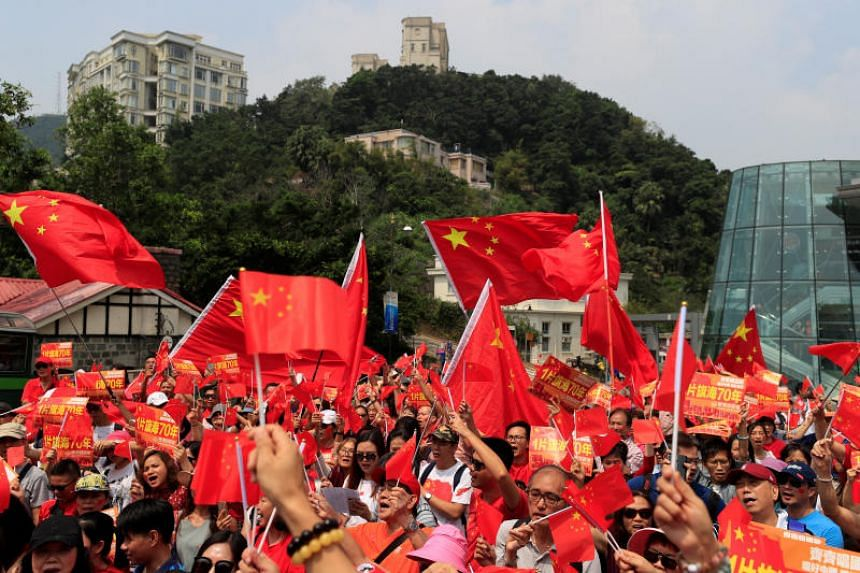 Pro-China supporters hold signs and Chinese national flags during a rally at Victoria Peak in Hong Kong, on Sept 29, 2019.