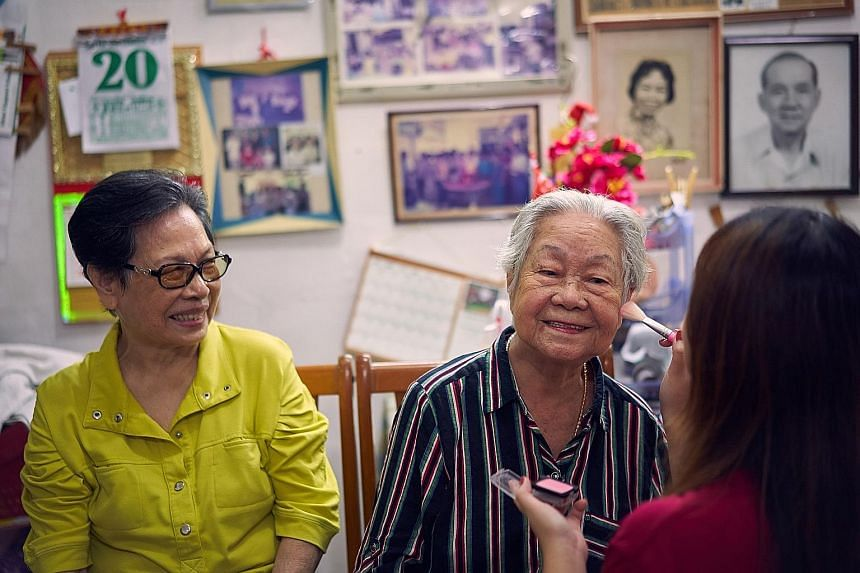 Madam Tan and Madam Poon visiting Clifford Pier, accompanied by staff from the Home Nursing Foundation. ST PHOTO: KEVIN LIM Madam Tan Bock Eng (left), 80, watching as Madam Poon Soo Lan, 86, got her make-up done by a volunteer from the Home Nursing F