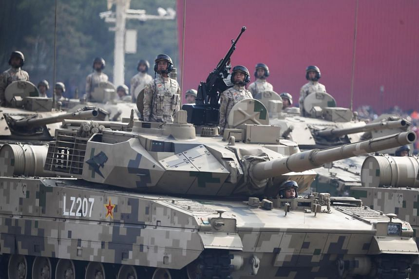 Chinese troops on tanks roll past Tiananmen Square during the military parade.