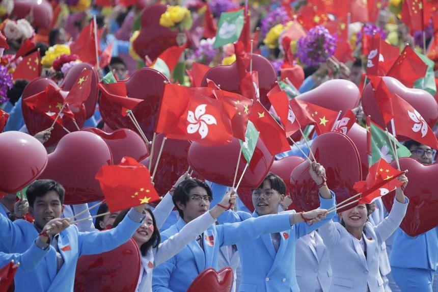 Performers waving the flags of China, Hong Kong and Macau during the military parade.