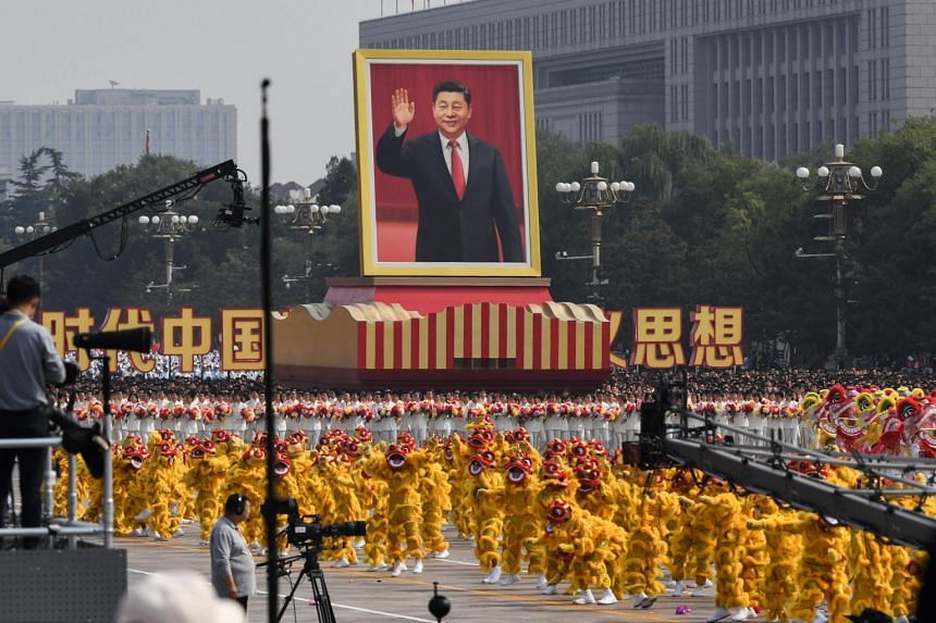 A float with a giant portrait of Chinese President Xi Jinping passes by Tiananmen Square.