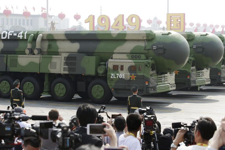 Military vehicles carrying DF-41 intercontinental ballistic missiles going past Tiananmen Square.